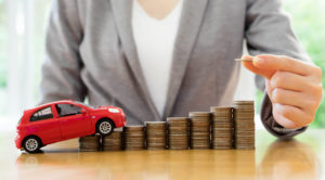 59638717 - businesswoman a toy car and a stack of coins